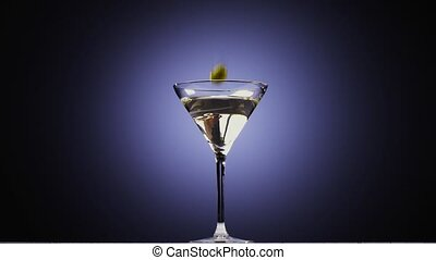 Two olives fall into tall glass with cocktail. Slow motion