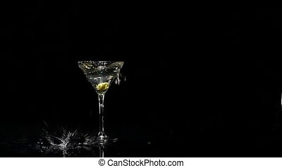 Two olives falling into a glass of martini. Slow motion.