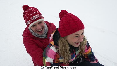 Slow-motion of cheerful friends riding a sled together