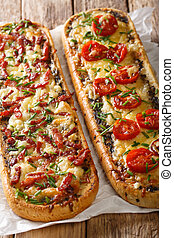 Two open casserole sandwiches with bacon, mushrooms, tomatoes and cheese close-up. vertical