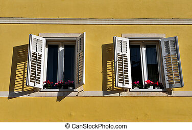Two open windows with flowers in old town