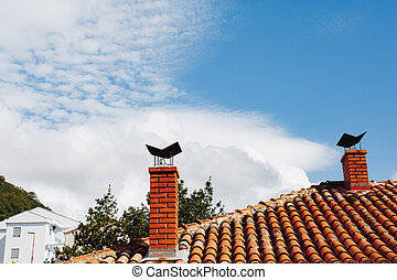 Two orange brick chimneys on a tile roof and against the backdrop of a white house and a blue sky.
