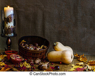 Two orange butternut squash and walnuts with autumn dry leaves on wooden background fall still life.