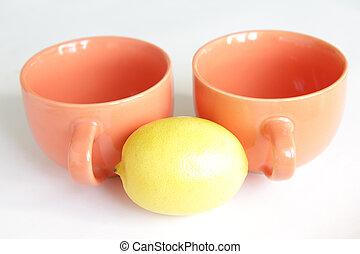 Two orange empty tea cups with lemo