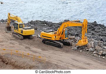 Two orange excavators near the sea