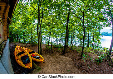 two orange kayaks standing near cabin by the lake