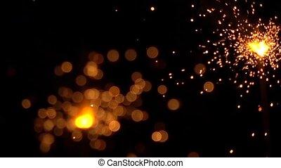 Two orange sparklers against dark background. Super slow motion shallow focus video, 500 fps