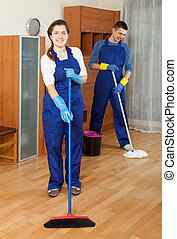 Two ordinary cleaners cleaning floor in room