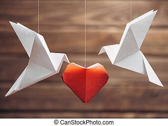 Two origami dove around paper heart.