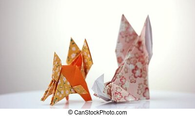Two origami foxes. Cute designed paper figurines of animals.