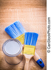two paint brushes and can on wooden board