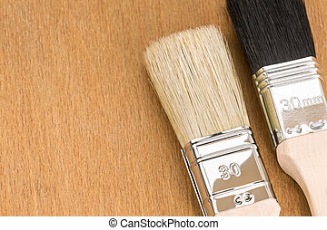 two paint brushes on wooden background