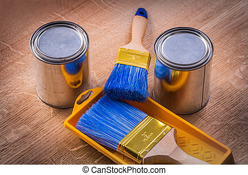 two paint cans brushes tray on wooden board construction concept