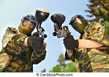 two paintball players in protective clothing aiming guns...