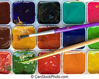 Two paintbrushes lying on watercolor pallet