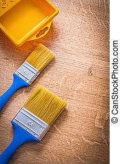two paintbrushes with blue handles and yellow paint can on woode