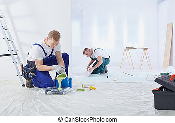 Two painters painting the wall