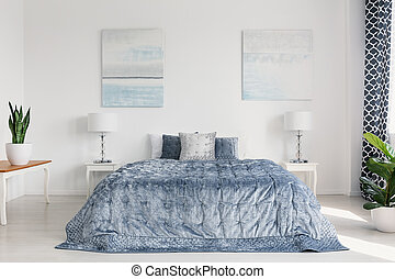 Two painting on the wall of elegant bright bedroom interior with cozy bedding and white furniture