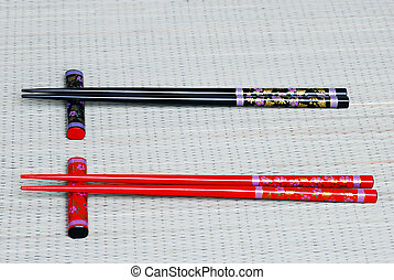 Two Pairs of Chop Sticks on bamboo mat