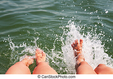 Two pairs of feet splash in the water