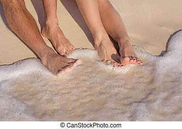 Two pairs of legs on white sand