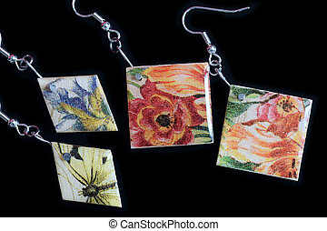 Two pairs of wooden earrings with a floral print on a dark background close up