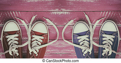 Two pairs of worn sneakers on a pink old wooden surface