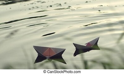 Two paper boats adrift in the river.