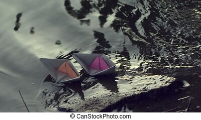 Two paper boats moored to the shore. - Two paper boats...