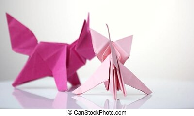 Two paper colorful foxes. Origami animal models made of pink...