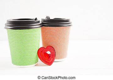 Two paper cups - red and green with heart between them