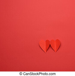 two paper hearts on a red background