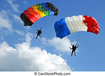 Facing two colored parachutes on blue sky with clouds.