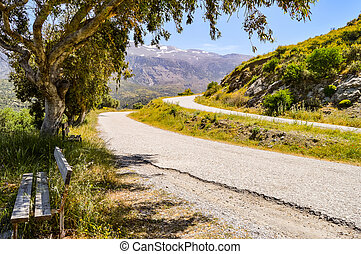 Two parallel mountain roads in Crete with a wooden bench