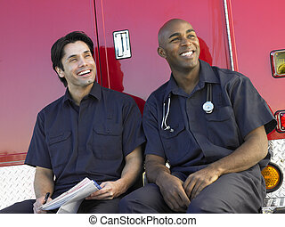 Two paramedics cheerfully doing paperwork, sitting by their...
