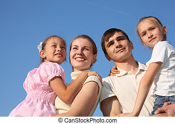 two parents hold children on hands against sky