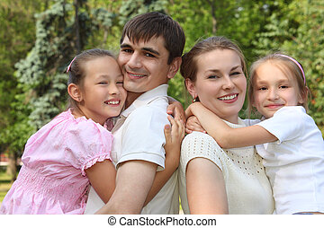 two parents hold children on hands