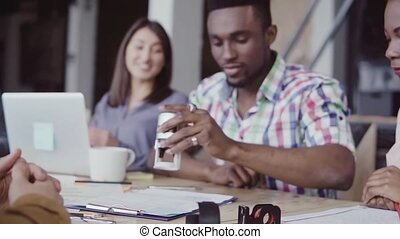 Two partners, african and caucasian sign a contract. Group...