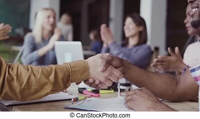 Two partners, african and caucasian businessmen shake hands....