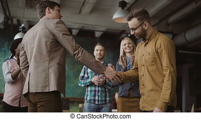 Two partners, businessman shake hands. Group of people...