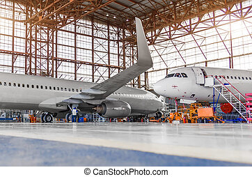 Two passenger aircraft for maintenance and repair in the hangar.