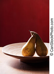 two pears in a wooden bowl