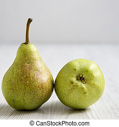 Two pears on a white wooden background, side view. Close-up.