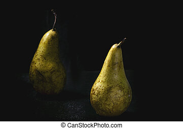 Two pears over wet black background