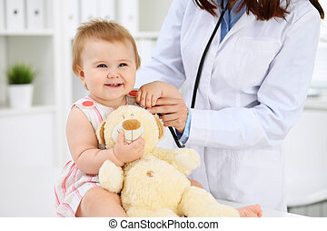 Two pediatricians are taking care of baby in hospital. Little girl is being examining by doctor with stethoscope. Health care, insurance and help concept