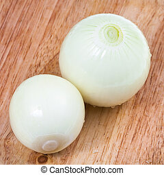 two peeled onions bulbs on cutting board