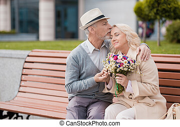 Two pensioners are sitting on a bench in the alley. An elderly man gently kisses a woman on the forehead