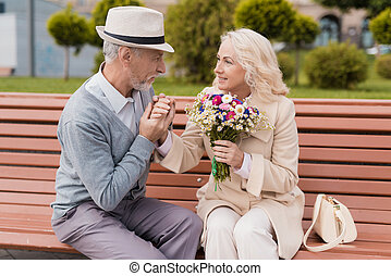 Two pensioners are sitting on a bench in the alley. An elderly man gently kisses a woman's hand