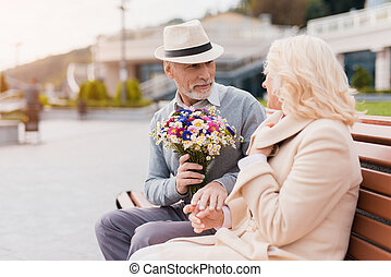 Two pensioners are sitting on a bench in the alley. An elderly man gives a woman flowers