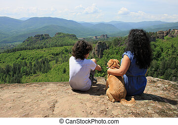 Two people and a dog sitting on a rock